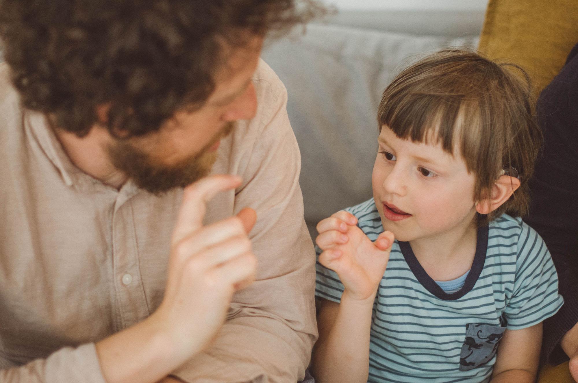 Ein Vater spricht mit Sohn gehörlosen Sprache, fotoshooting familie Freiburg