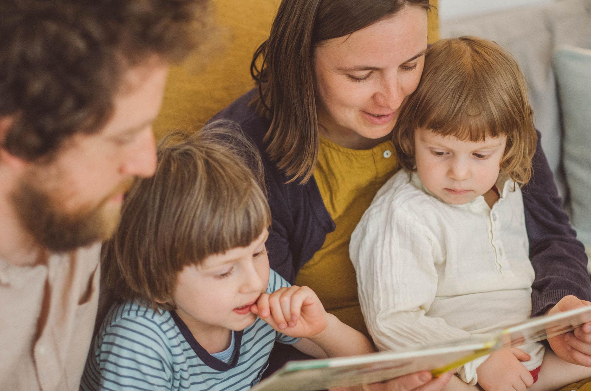 fotoshooting familie, Eltern lesen den Kindern vor