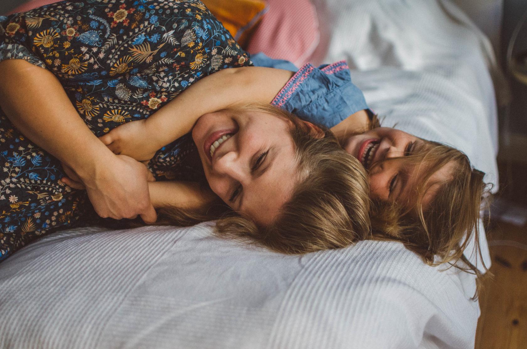 Mutter tobt mit Tochter auf dem Bett bei Schwangerschafts Fotoshooting Basel