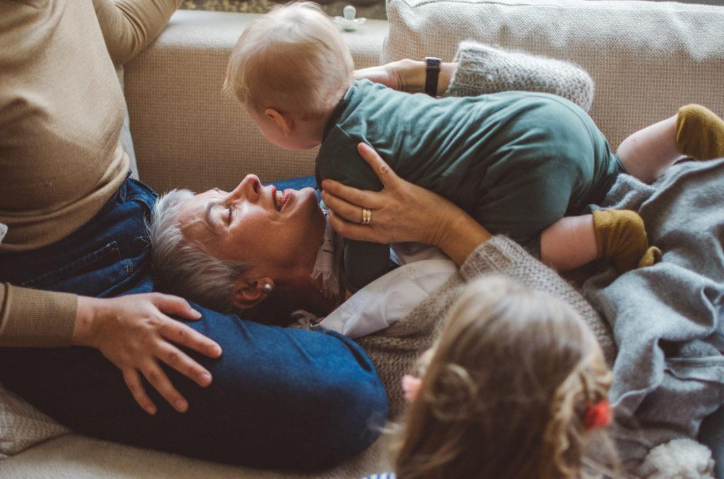 Eine Mutter mit ihrer Mutter und den Kindern auf dem Sofa entstanden bei einem Familienfotoshooting Freiburg