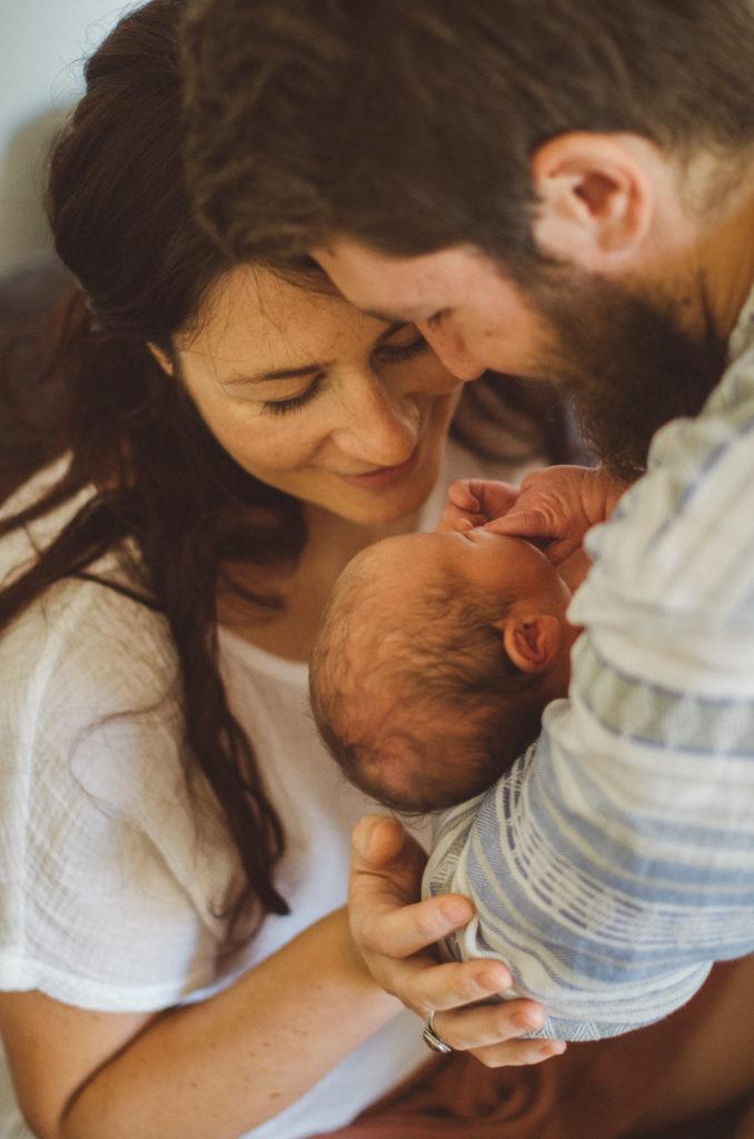 Mutter und Vater betrachten ihr Neugeborenes entstanden bei einem Neugeborenenfotoshooting Freiburg