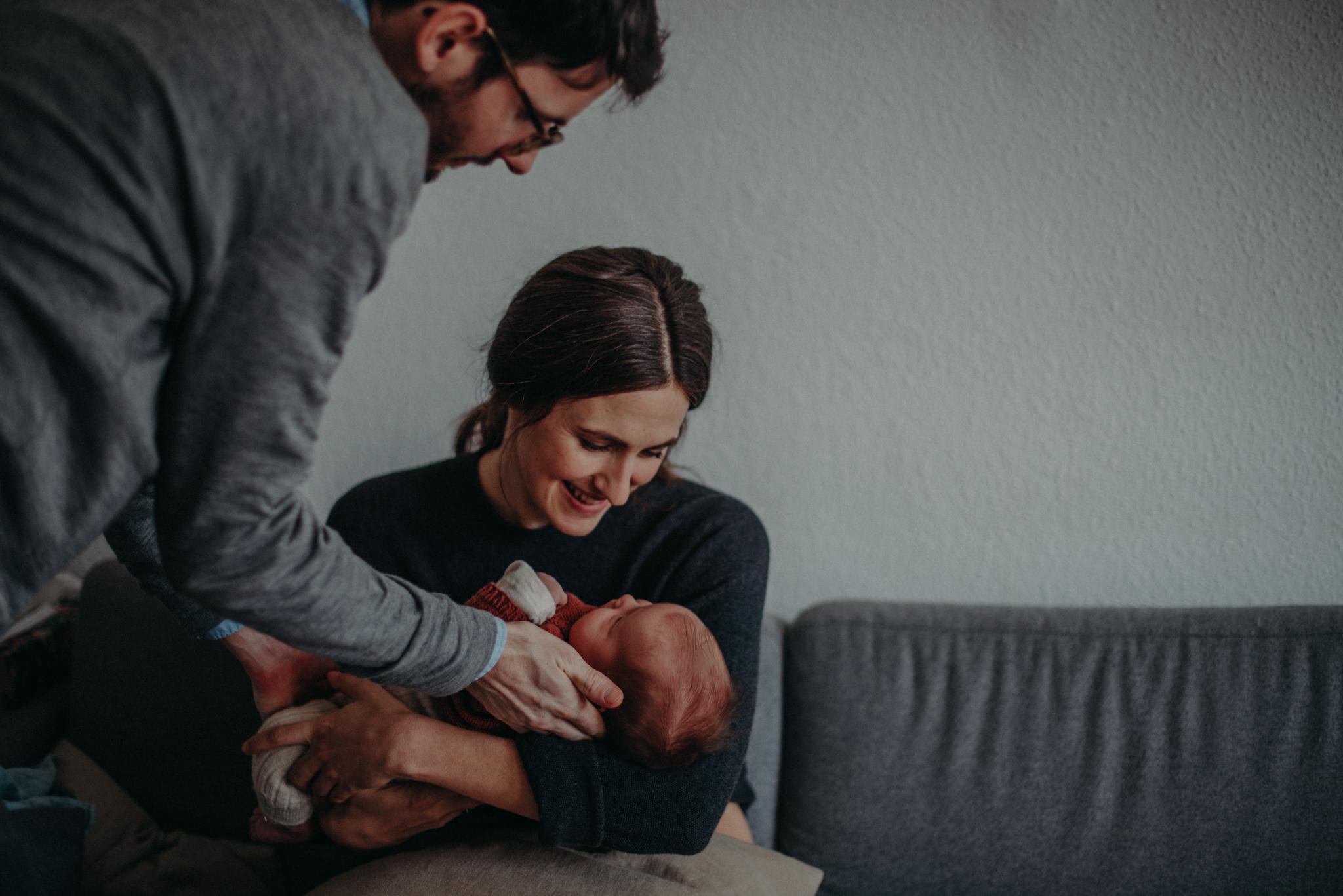 Familienfoto mit Neugeborenen entstanden bei Babyfotoshooting Zuhause in Freiburg