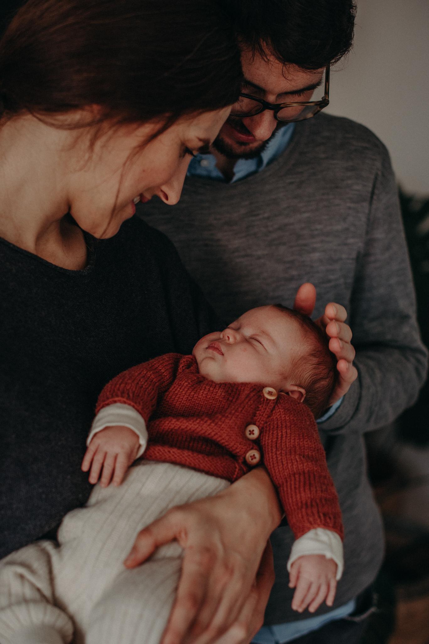 Familienfoto Neugeborenenfoto von schlafendem Baby auf dem Arm der Eltern entstanden bei Babyfotoshooting Zuhause in Freiburg