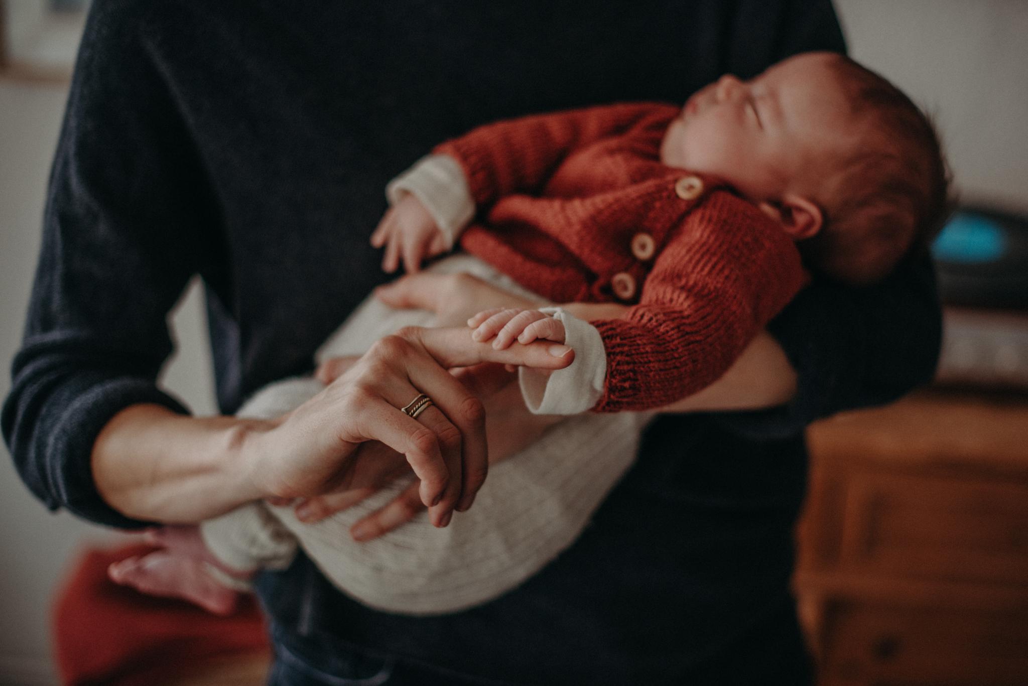 Neugeborenenfoto von schlafendem Baby auf dem Arm der Mutter entstanden bei Babyfotoshooting Zuhause in Freiburg