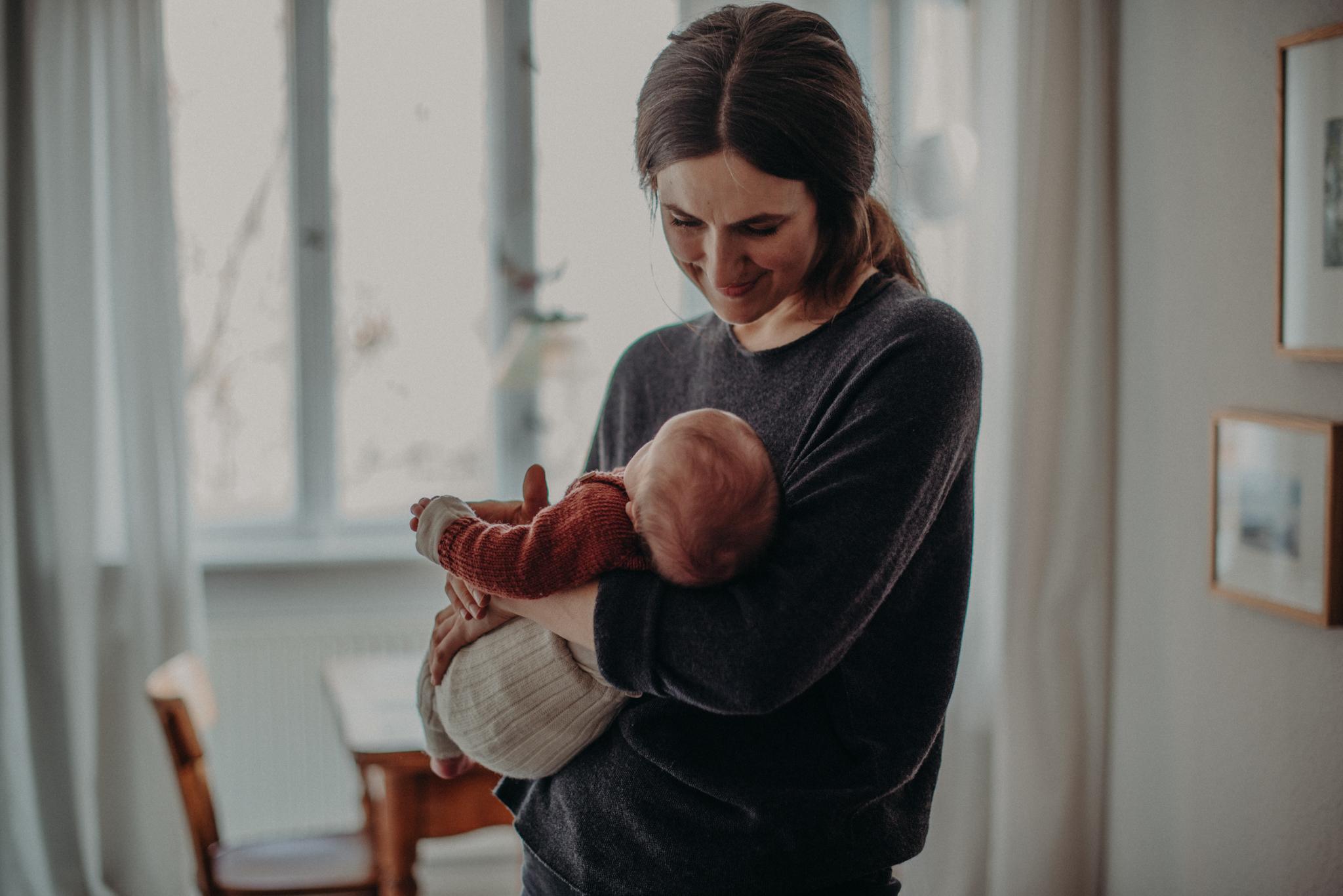 Natürliches Neugeborenenfoto von schlafendem Baby entstanden im Arm der Mutter bei Babyfotoshooting Zuhause in Freiburg
