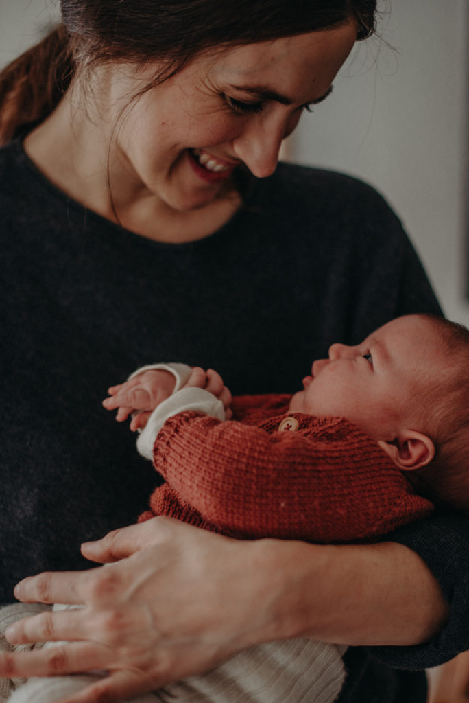 Natürliches Neugeborenenfoto von Baby im Arm der Mutter bei Babyfotoshooting Zuhause in Freiburg, Fotografin Freiburg