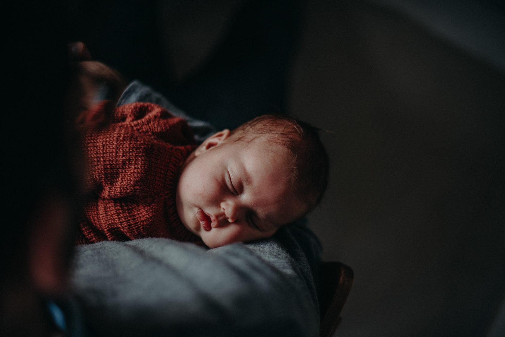 Natürliches Neugeborenenfoto von Baby im Arm der Mutter entstanden bei einem Babyfotoshooting Zuhause im Wochenbett in Freiburg