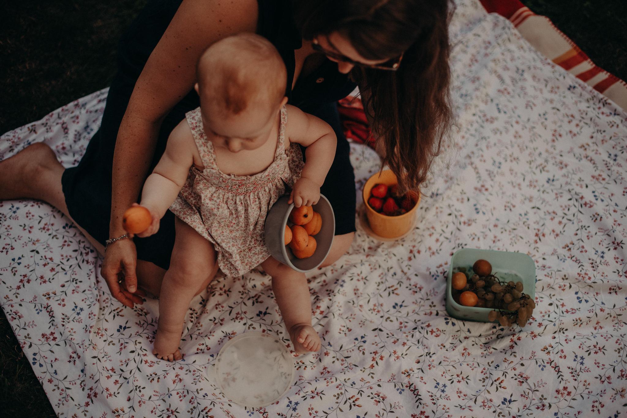 Mutter und Tochter mit Pfirsichen im Garten, natürliches Familienfoto entstanden bei Familienfotoshooting in Freiburg