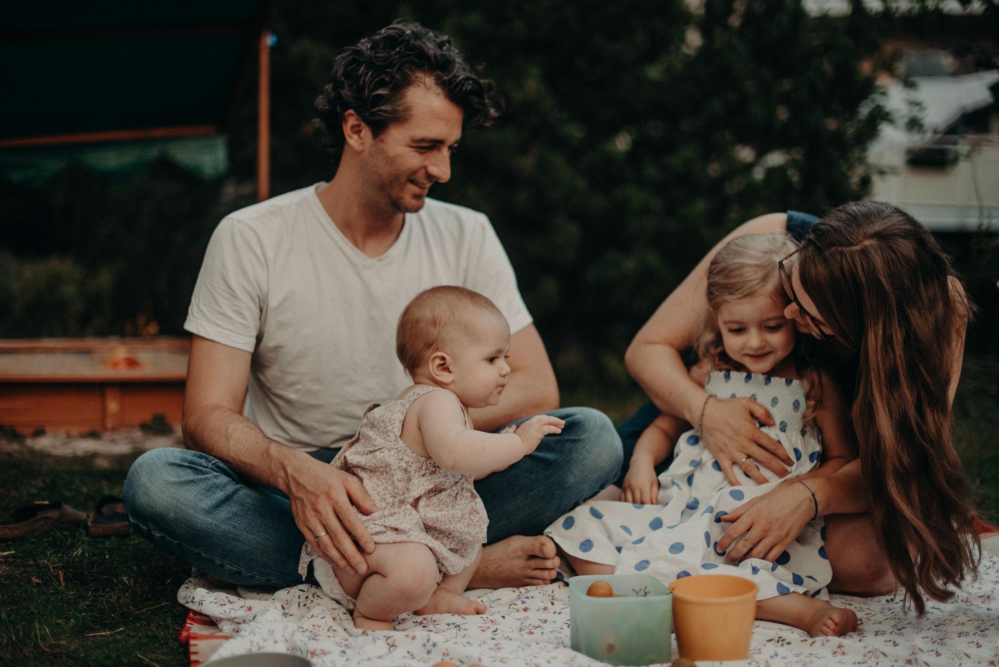 Familie auf Picknickdecke im Garten, natürliches Familienfoto entstanden bei Familienfotoshooting in Freiburg