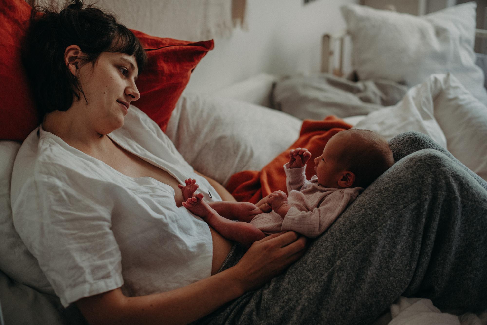 Mutter mit Neugeborenen im Wochenbett, Blogpost Babyfotoshooting selber machen, Fotografin Freiburg