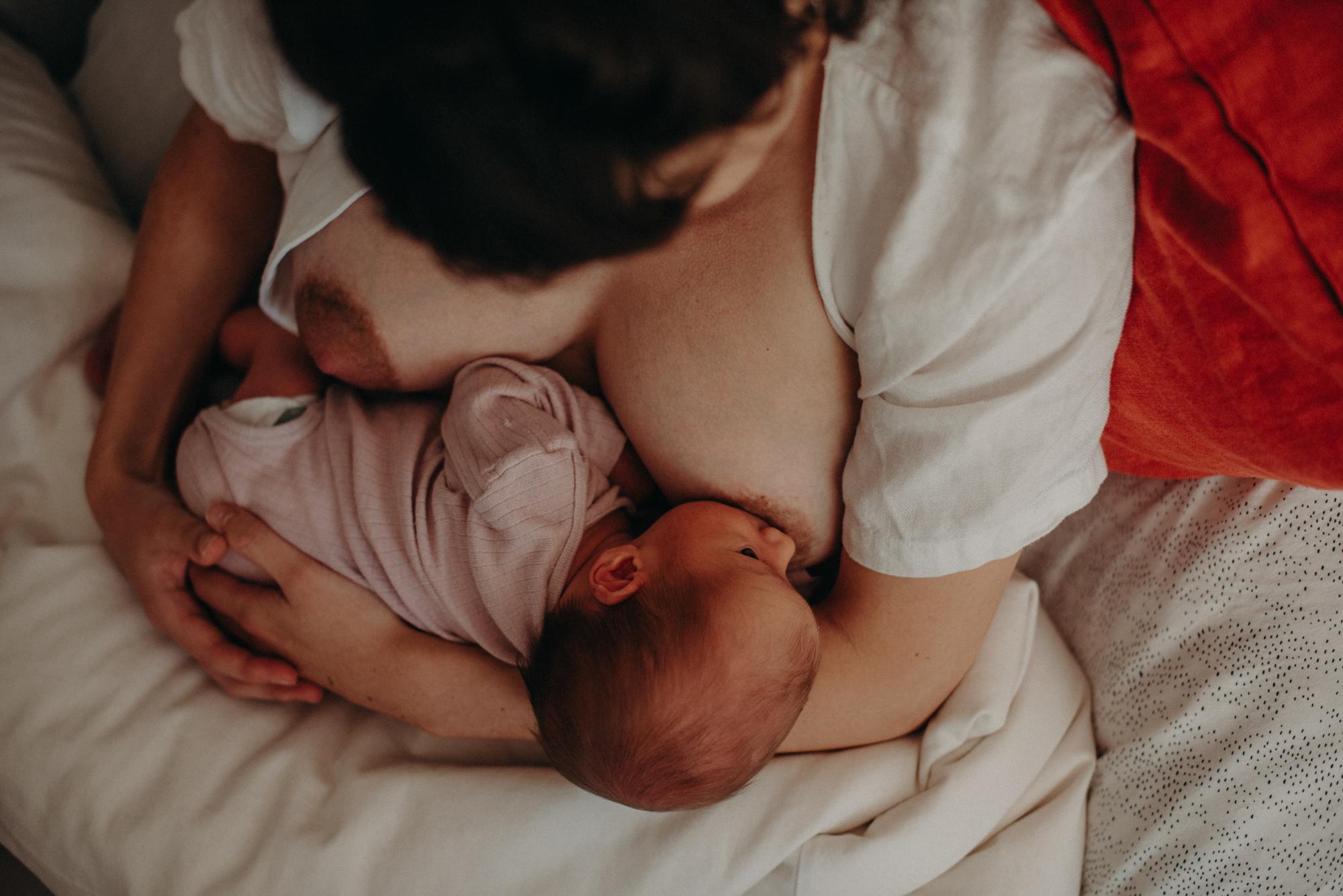 Mutter stillt Neugeborenes, Blogpost Babyfotoshooting selber machen, Fotografin Freiburg