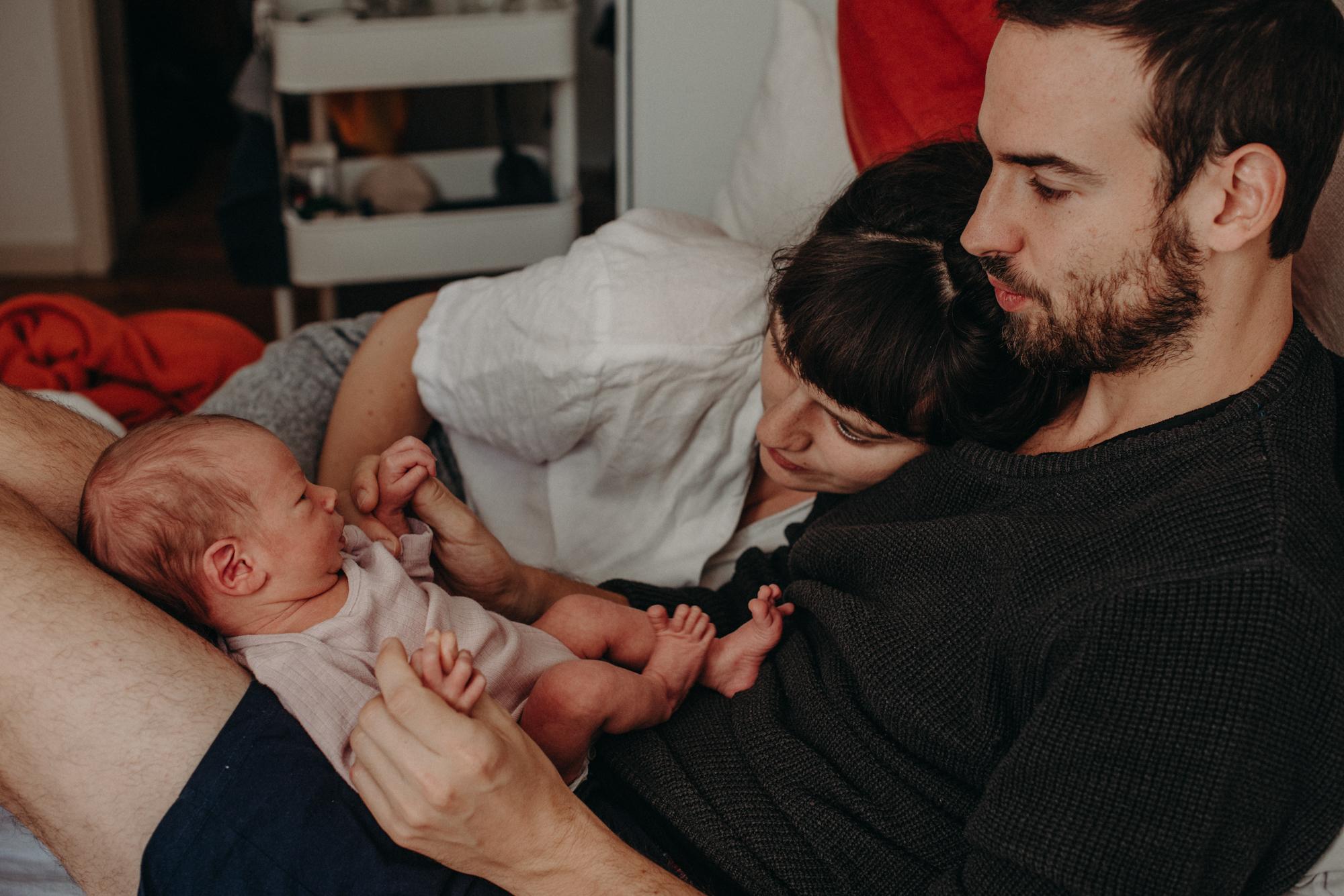 Eltern betrachten ihr Neugeborenes Baby im Wochenbett, Blogpost Babyfotoshooting selber machen, Fotografin Freiburg