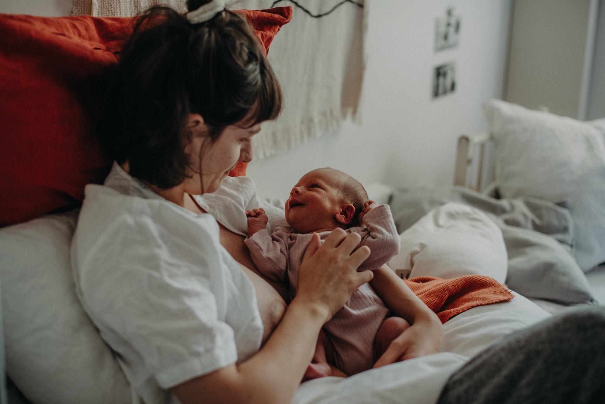 Ein Neugeborenes lächelt die Mutter an, Blogpost Babyfotoshooting selber machen, Fotografin Freiburg